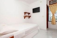 Habitación, dotada con TV, cama, repisa y mesa auxiliar.