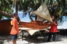 Graduates pose with a large scale model canoe at the graduation.