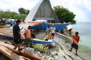 Stripped banana fronds make the moving of the big canoe easier 083