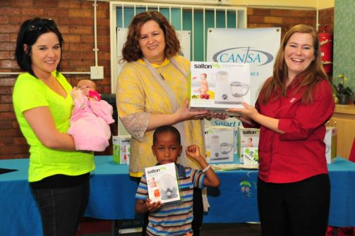 Vera van Dalen receiving product from Samantha van Jaarsveld, Category Manager: Kitchen Appliances for Home of Living Brands with a volunteer moms at the Nicus Lodge and also the little ones.