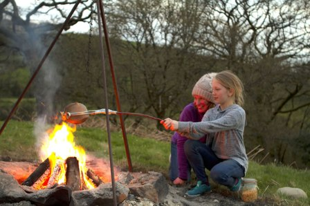 A photo of a mother and daughter cooking popcorn over a campfire in the glamping field