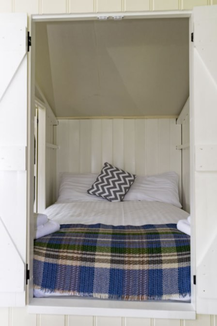 An image of the cosy cabin bed with Welsh blanket in Afon