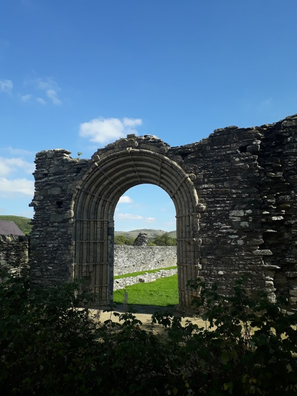 Strata Florida, an ancient stone arch, with the countryside beyon