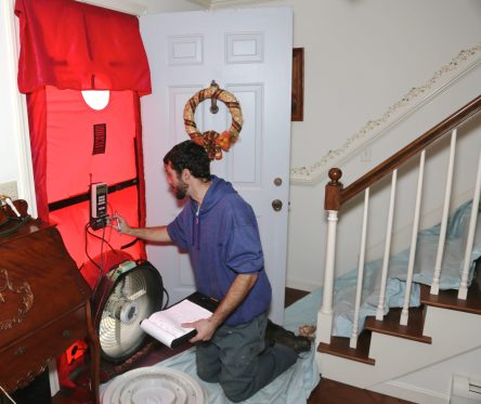 A blower door test is performed to de-pressurize the house to help determine air leaks.