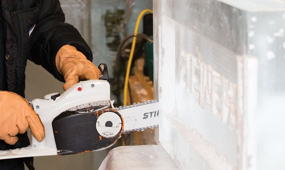 sculpting a piece of ice with a chainsaw