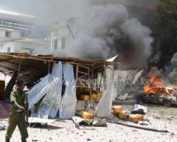 A Somali policeman walks past a burning car on April 14, 2013, in Mogadishu, after a suicide bomber attack in the regional court premises that left several dead/AFP