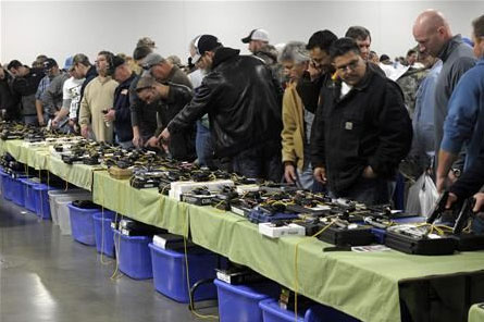 People look over a table of handguns for sale at a gun show in Kansas City, Missouri December 22, 2012. (REUTERS/Dave Kaup)