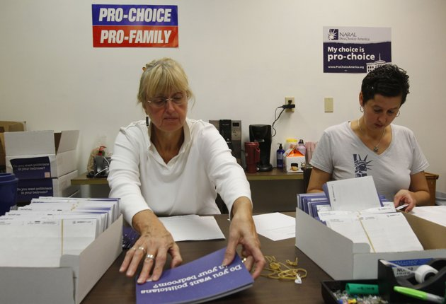 """NARAL Pro-Choice New Hampshire volunteer Gail Laker-Phelps (L) and NARAL Pro-Choice New Hampshire Campaign Director Melissa Bernardin put address labels mailers which read, """"Do you want politicians in your bedroom?"""" in Concord, New Hampshire October 27, 2012.  REUTERS/Jessica Rinaldi"""