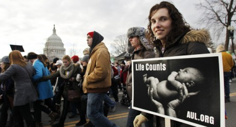 Rebecca Purdy, right, of Philadelphia join anti-abortion activists as they march in front of the U.S. Supreme Court, near the U.S. Capitol, background, in Washington, Monday, Jan. 24, 2011, during a rally against Roe v. Wade on the anniversary of the U.S. Supreme Court decision.   (AP Photo/Manuel Balce Ceneta)