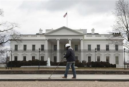 A worker cleans a sidewalk outside the White House in Washington March 2, 2013. (REUTERS/Yuri Gripas)