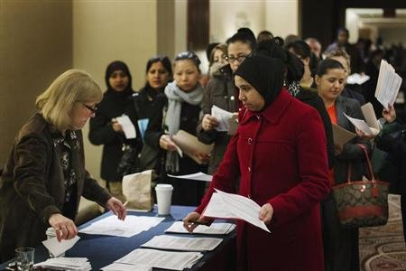 Job seekers adjust their paperwork as they wait in line to attend a job fair in New York.  (REUTERS/Lucas Jackson)