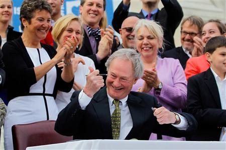 Rhode Island Governor Lincoln Chafee uncaps his pen as he signs the Marriage Equality Act into law at the State House in Providence, Rhode Island.  (REUTERS/Jessica Rinaldi)