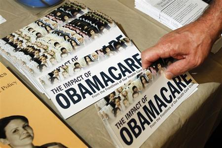 """A Tea Party member reaches for a pamphlet titled """"The Impact of Obamacare"""", at a """"Food for Free Minds Tea Party Rally"""" in Littleton, New Hampshire.  REUTERS/Jessica Rinaldi//Files"""