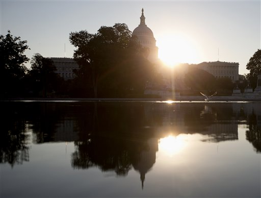 The sun rises behind the Capitol in Washington, Wednesday. (AP Photo/Carolyn Kaster)