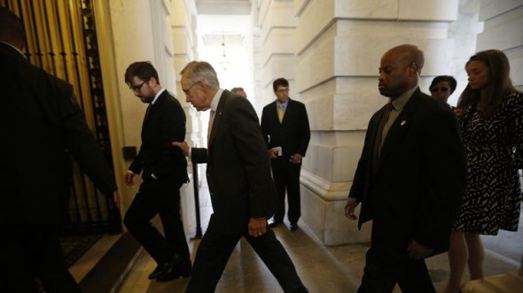 Senate Majority Leader Harry Reid (D-NV) is ushered by his security team. (REUTERS/Jason Reed)