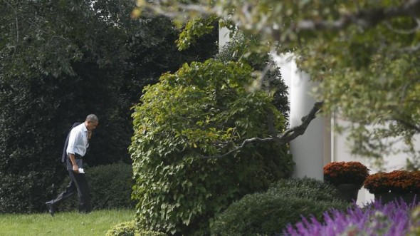 President Barack Obama walks back to the Oval Office after visit to Martha's Table, which assists the poor and where furloughed federal employees are volunteering. (AP/Charles Dharapak)