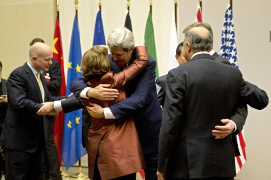 Secretary of State John Kerry embraces EU foreign policy after UN ceremony in Geneva on new deal with Iran. (AP/Keystone,Martial Trezzini)