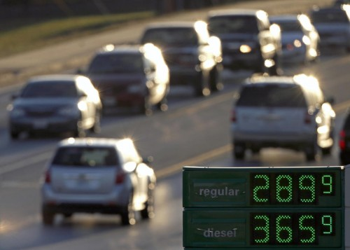 Motorists drive past a gas station selling regular unleaded gasoline for less than $3.00 a gallon, in Independence, Mo. (AP Photo/Charlie Riedel)