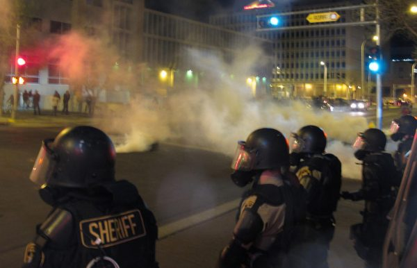 Riot police launch tear gas toward activists in downtown Albuquerque, N.M. following a 10-hour protest around the city, Sunday, March 30.  (AP Photo/Russell Contreras)