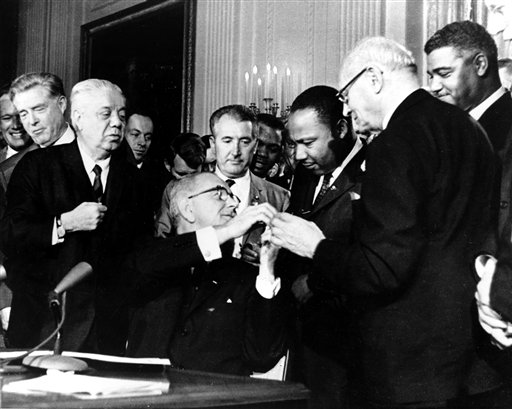 President Lyndon B. Johnson reaches to shake hands with Dr. Martin Luther King Jr. after presenting the civil rights leader with one of the 72 pens used to sign the Civil Rights Act in Washington in 1964.  (AP Photo)