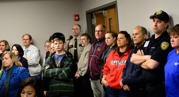 Students, parents and community members stand in the back of the room to listen as Waseca Police Captain Kris Markeson and Waseca school Superintendent Tom Lee speak at a news conference about the 17-year-old arrested in a plot to kill his family and massacre students. (AP Photo/The Star Tribune,Glen Stubbe)