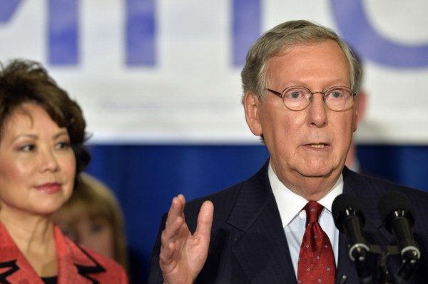 With his wife Elaine Chao, left, looking on, Kentucky Senator Mitch McConnell addresses his supporters following his victory in the republican primary, Tuesday.  (AP Photo/Timothy D. Easley)