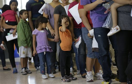 Immigrants who entered the U.S. illegally stand in line for tickets at the bus station.  (AP Photo/Eric Gay)