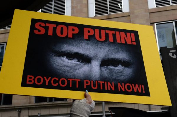A member of the Australian Ukrainian community raises a placard witha picture of Russian President Vladimir Putin during a rally in Sydney on July 19, 2014 calling for Putin not to be allowed to come to Australia for a November G20 leaders summit  (AFP Photo/Saeed Khan)