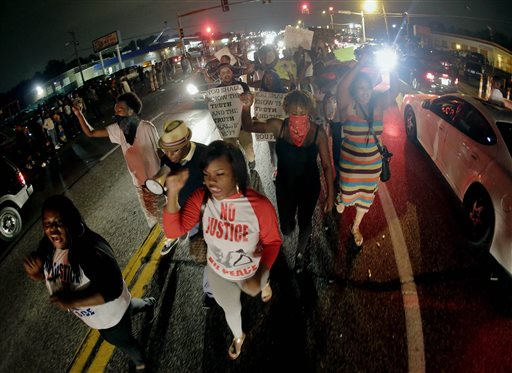 Protesters march down the middle of a street in front of a convenience store in Ferguson, Mo.  (AP Photo/Charlie Riedel)