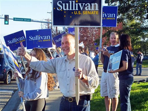 Dan Sullivan, candidate for the Republican candidate for election to the U.S. Senate, waves signs along a busy street on the morning of Alaska's primary election Tuesday (AP Photo/Becky Bohrer)