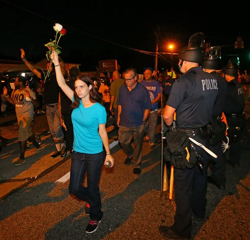 A protester holds roses in the air as she marches with others past police officers in Ferguson, Mo.  (AP Photo/Atlanta Journal-Constitution, Curtis Compton)