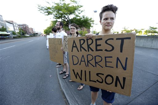 "Protester Hana Kato, of Tacoma, Wash., holds a sign that reads ""Arrest Darren Wilson"" as she attends an evening rally Tuesday (AP Photo/Ted S. Warren)"