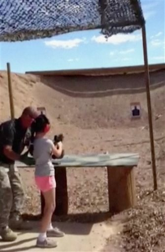Firing-range instructor Charles Vacca, left, shows a 9-year old girl how to use an Uzi. Vacca, 39, and was standing next to the girl on Monday at the Last Stop range in Arizona, south of Las Vegas, when the girl squeezed the trigger, causing the Uzi to recoil upward and shoot Vacca in the head.  (AP Photo/Mohave County Sheriff Department)
