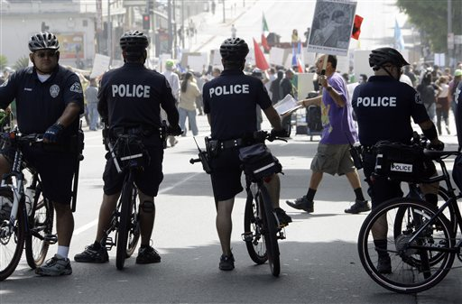 Police officers on bicycles keep watch as demonstrators protesting several incidents of alleged Los Angeles Police Department brutality  (AP Photo/Reed Saxon)