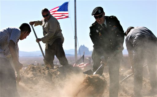 Maj. Xavier Miller of the New Mexico National Guard, second from right, leads family members and workers in burying Sgt. 1st Class Kenneth W. Westbrook at the veterans' section of the Shiprock, N.M. Community Cemetery.  (AP Photo/The Daily Times, Xavier Mascareñas)