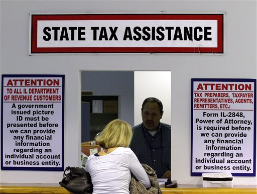An Illinois Department of Revenue employee offers assistance to income tax payers at the Illinois Department of Revenue in Springfield  (AP Photo/Seth Perlman)