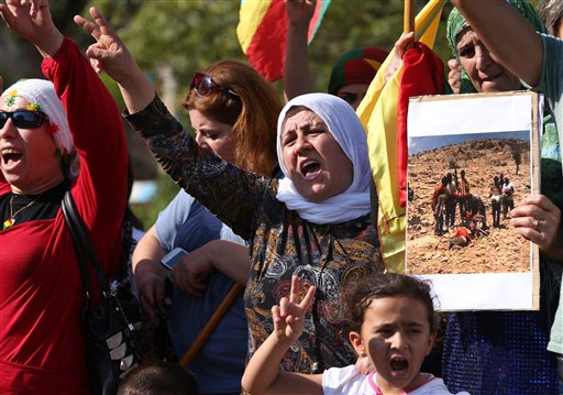 Kurdish citizens who live in Lebanon shout slogans and hold a photograph during a demonstration against militants who refer to themselves as the Islamic State, in front of the UN building, in downtown Beirut, Lebanon  (AP Photo/Hussein Malla)
