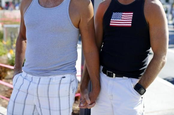 A gay couple holds hands during a rally in support of the United States Supreme Court decision on marriage rights in San Diego (REUTERS/Mike Blake)