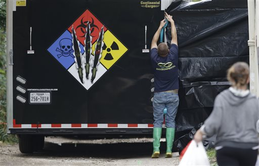A hazmat worker puts up a plastic sheet before starting to clean the apartment building of a hospital worker Sunday in Dallas.  (AP Photo/LM Otero)
