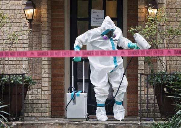 A member of the CG Environmental HazMat team disinfects the entrance to the residence of a health worker at the Texas Health Presbyterian Hospital who has contracted Ebola in Dallas (REUTERS/Jaime R. Carrero)