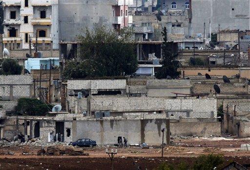 Kurdish fighters, bottom, enter their positions in a house in Kobani, Syria  (AP Photo/Lefteris Pitarakis)