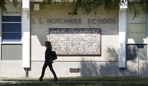 A woman walks by the front of L.L. Hotchkiss School  (AP Photo/LM Otero)