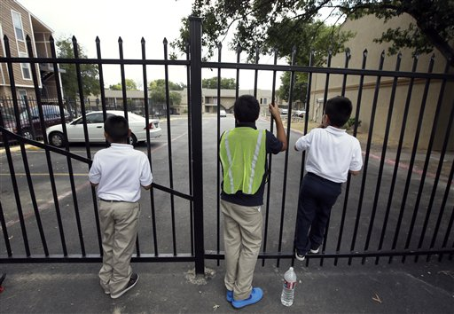 Three children on their way home from school stop to peer through the gate down at a building at The Ivy Apartments in Dallas where a man was diagnosed with having the Ebola virus was staying with family at the complex.  (AP Photo/Tony Gutierrez)