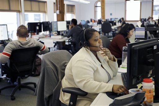 Loretha Cager talks with an applicant at MNSure's call center in St. Paul, Minn.  (AP Photo/Ann Heisenfelt)
