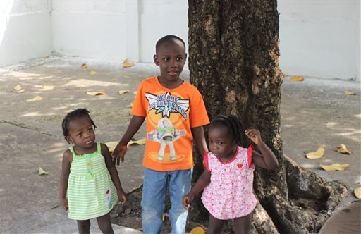 In this Dec. 2013 family photo provided by Tessa and Joel Sanborn, their adopted twins, Favor, left, and Faith, right, stand with their brother Devine, center, in Liberia at the time that the Sanborns traveled there to adopt Faith and Favor. The family is now waiting to travel to Liberia again to adopt Devine, but the Ebola epidemic has put adoptions in several west African countries on hold indefinitely (AP Photo/Courtesy Sanborn Family)