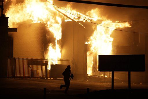 A man runs away from the burning storage facility after  the announcement of the grand jury decision Monday (AP Photo/David Goldman)