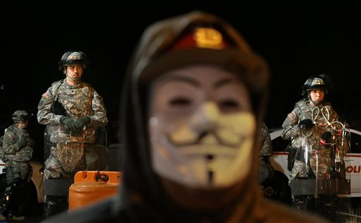 A lone protester stands in front of the Ferguson Police Department as National Guardsmen stand watch in the parking lot on Tuesday  (AP Photo/St. Louis Post-Dispatch, Robert Cohen)