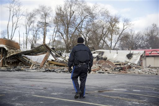 A members of the Missouri Highway Patrol walk past a building burned to the ground Tuesday  (AP Photo/Jeff Roberson)
