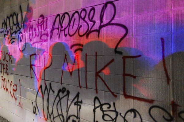 Police officers shadows are cast onto graffiti on the wall of a Subway during the second night of demonstrations in Oakland, California, following the grand jury decision in the shooting of Michael Brown in Ferguson, Missouri (REUTERS/Elijah Nouvelage)