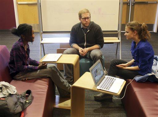 English teacher Tom Rademacher talks with his high school juniors Kierra Murray, left, and Ana Silverman, right, Tuesday  (AP Photo/Jim Mone)